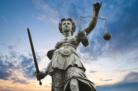 justice statue with sword and scale. cloudy sky in the backgroun
